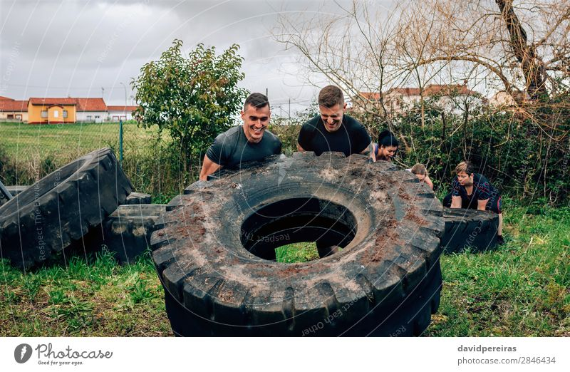 Participants in obstacle course turning truck wheel Sports Human being Woman Adults Man Group Authentic Strong Power Effort Competition Teamwork