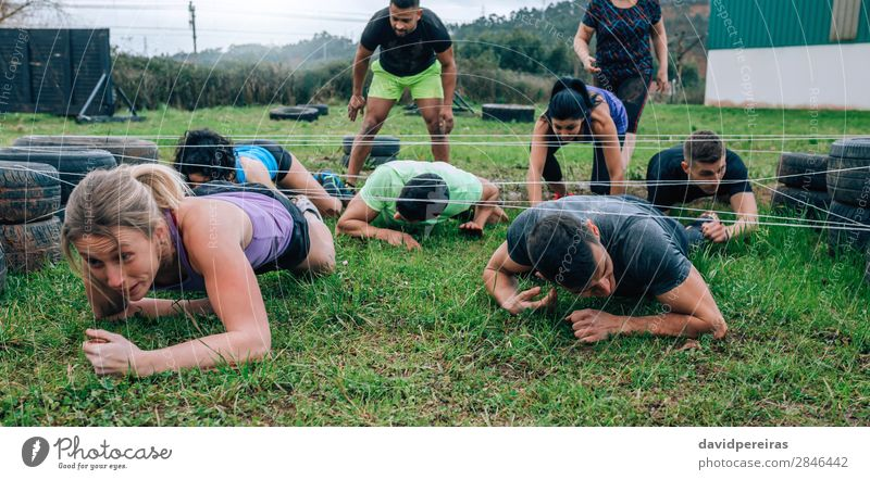 Participants in an obstacle course crawling Sports Human being Woman Adults Man Group Meadow To enjoy Black Effort Competition Barbed wire electrified cable