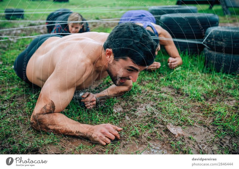 Male participant in an obstacle course crawling Joy Happy Sports Success Human being Woman Adults Man Group Authentic Dirty Effort Competition Mud