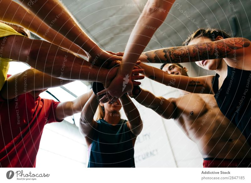 Sportive people stacking hands sportsmen Together Gymnasium Teamwork achievement unity Support Body building Cheerful Muscular Energy Determination Gesture