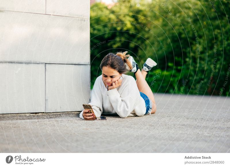 Girl browsing phone while lying on ground Woman Youth (Young adults) PDA youngster Technology Internet Connection Culture leaning on hand using Hipster Summer