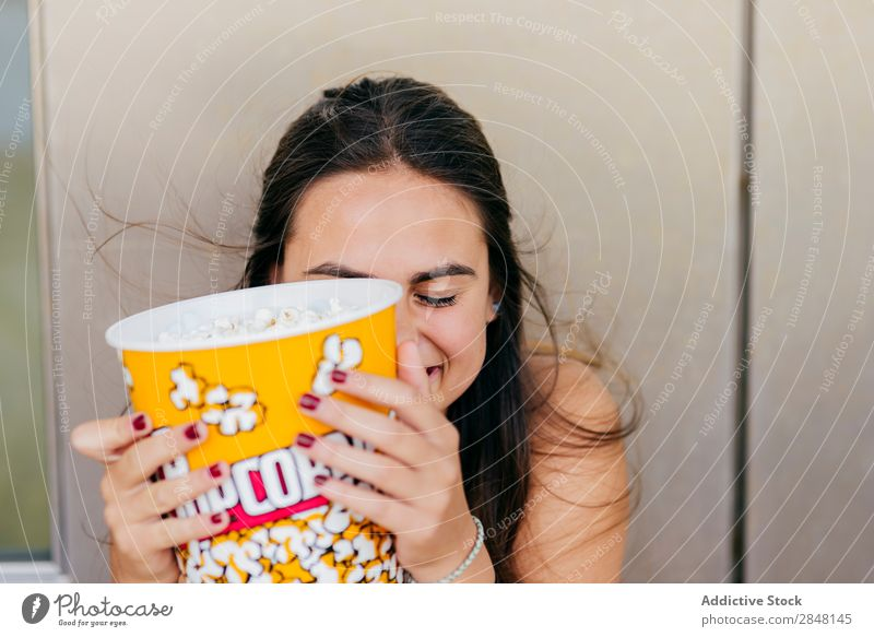 Lovely girl posing with popcorn Woman youngster Popcorn Laughter Joy Town Cheerful Bucket Playful Hipster Style Clothing Portrait photograph covering face
