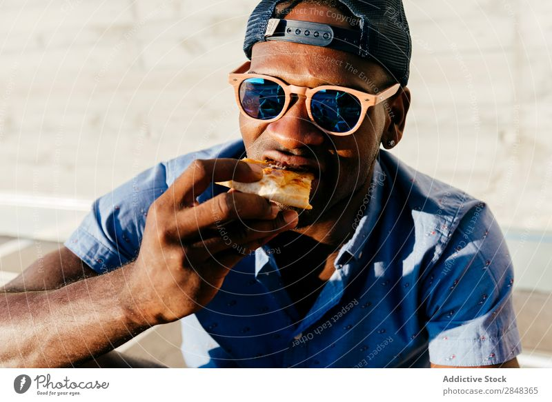 Young black man eating pizza at street Man Style Pizza Street Portrait photograph Black enjoying Food Lunch Lifestyle Student Hip & trendy handsome