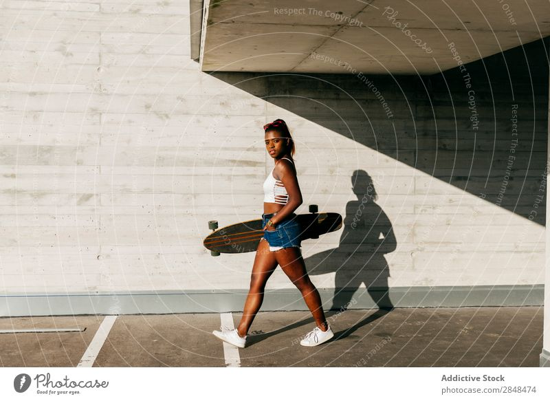 Stylish woman with board walking at street Woman Longboard Town Sports Leisure and hobbies skateboarder Black Skateboarding Youth (Young adults) African Modern