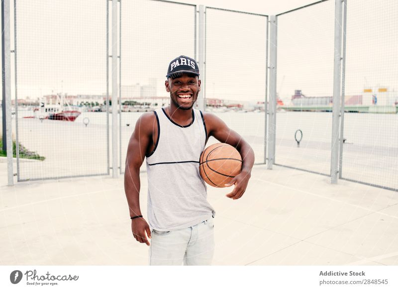 Black man with basketball Man Basketball Ball outstretching street ball Self-confident Sports ground Town Masculine Street sportsman Style Posture