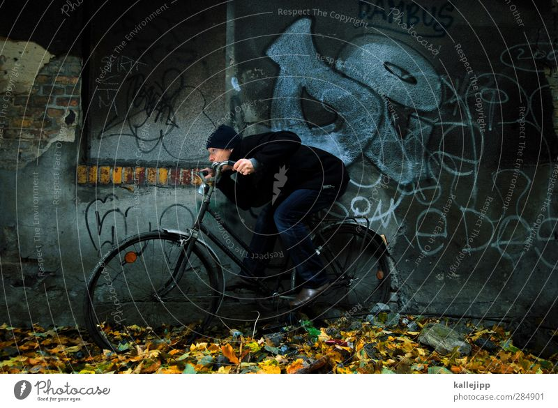 headwind Bicycle Human being Masculine Man Adults 1 30 - 45 years Autumn Vehicle Driving Steering Haste Speed Wall (barrier) Graffiti Leaf Duck down
