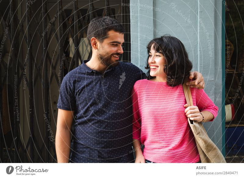 Happy young couple smiling at each other Lifestyle Shopping Joy Beautiful Summer Woman Adults Man Friendship Couple Street T-shirt Sweater Brunette Beard