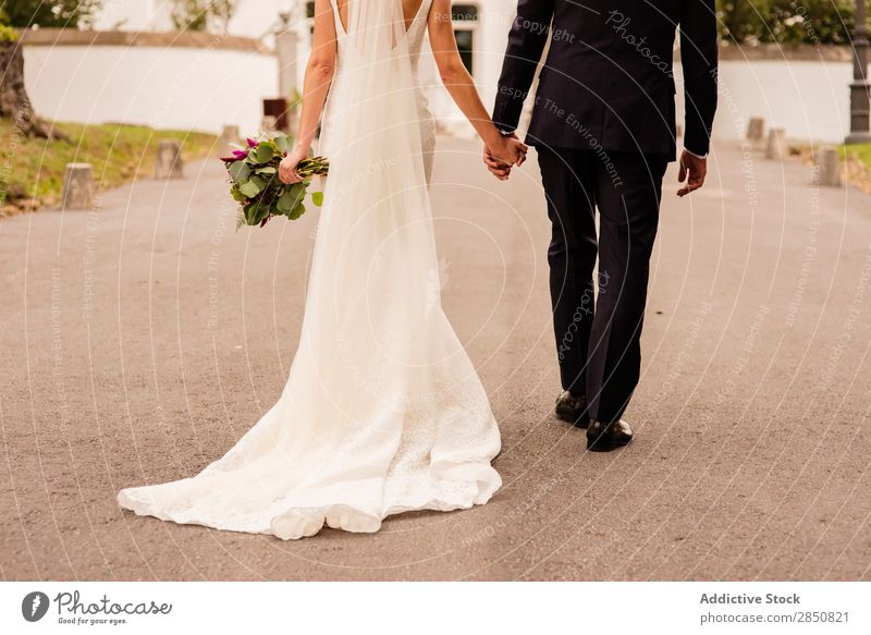 Crop stylish bride and groom walking on street Couple Elegant Bride Bouquet Ceremony Harmonious Veil