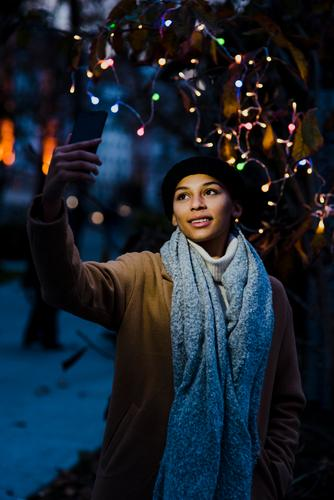 Woman taking selfie near tree with lights Selfie Light Beautiful Youth (Young adults) Portrait photograph Human being Tree PDA Easygoing Mobile Smiling pretty