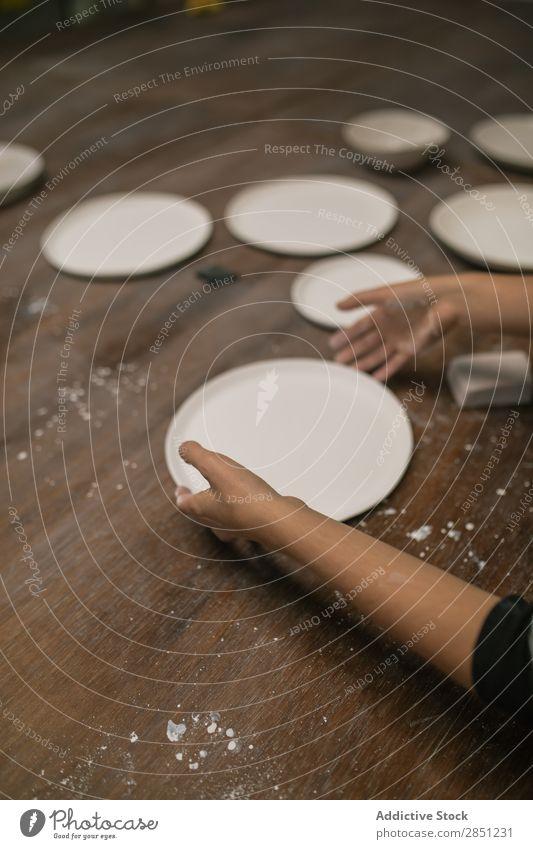 Crop person working with ceramic plate Human being Workshop Plate Crockery handwork Desk Make Clay utensil Art Enamel Creativity Handicraft glaze clay ware