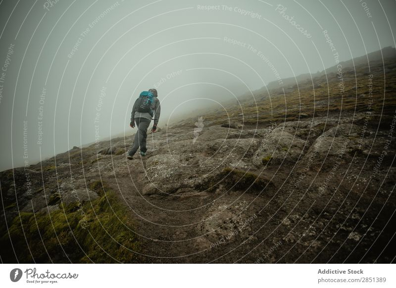 Man walking on rocky green slope of hill Landscape Hill Rock Wilderness Valley Fog Slope Mountain Vacation & Travel Weather tranquil Seasons Environment Nature