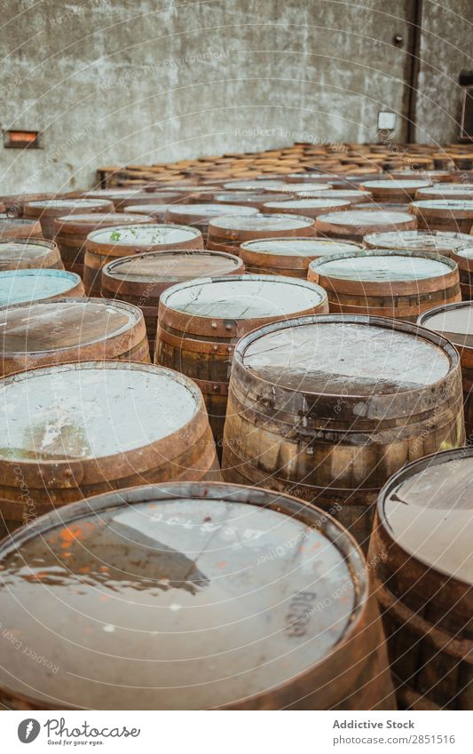 Wooden barrels on stone surface Arranged Winery Storage Production Factory Warehouse Alcoholic drinks Beverage Stack Collection Rustic Arrangement Pavement