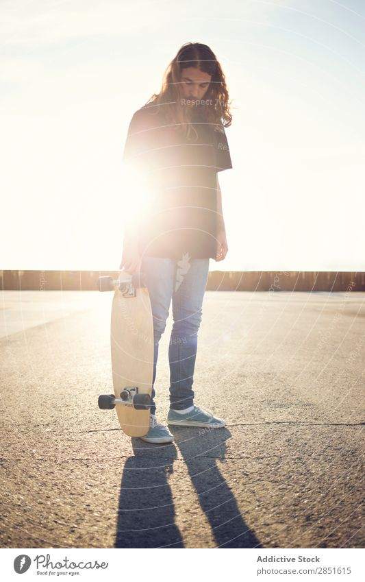 Man posing with skateboard in evening Skateboarding Ice-skating long hair Square Asphalt Evening Sunset skateboarder Youth (Young adults) Lifestyle Joy Extreme