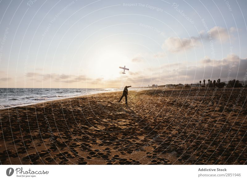 An unrecognizable man on a beach throwing the toy plane Human being Airplane Playing Throw Story Beach Happy Joy Toys Lifestyle Dream Childish Man Evening Coast