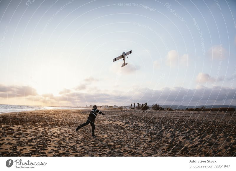 Man on a beach throwing the toy plane Human being Airplane Playing Throw Story Beach Happy Joy Toys Lifestyle Dream Childish Evening Coast Ocean Water Intellect