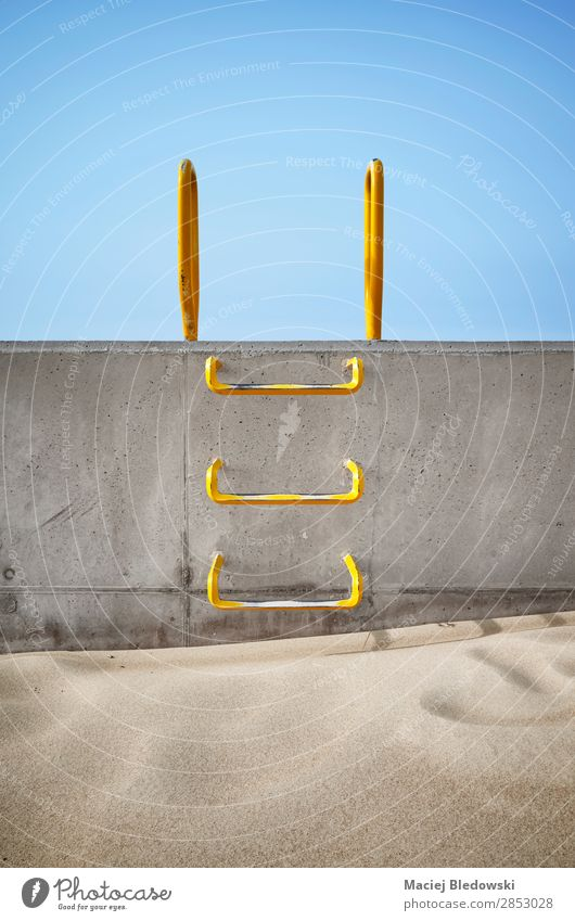 Steel ladder embedded in a concrete wall. Sand Sky Concrete Metal Blue Bravery Willpower Acceptance Help Curiosity Interest Hope Dream Inhibition Fear