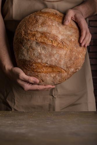 Man holding a freshly baked loaf of bread Baking Bakery Bread Breakfast carbohydrate Cut Dark Flour Food Fresh Hand Self-made home-baked Home-made Rustic Seed