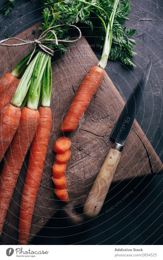 Fresh carrots in a wooden cutting board Background picture bunche Carrot Multicoloured Dark Food Harvest Healthy Knives Metal Nutrition Orange Organic Raw