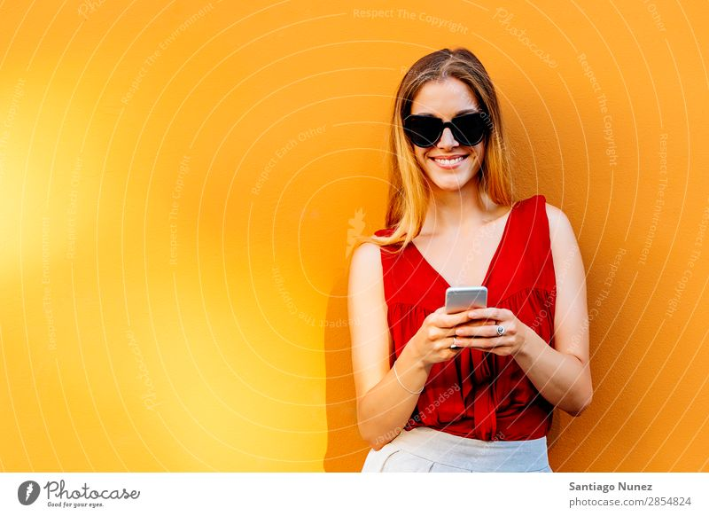 Portrait of beautiful young woman using mobile phone in the street. Woman Telephone Happy Mobile Youth (Young adults) Wall (building) Cellphone