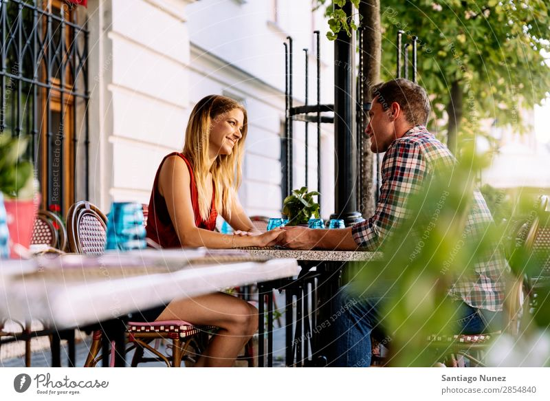 Young Couple having fun in the City. Sit Relationship Love Youth (Young adults) Hold Hand Looking Happy Laughter Restaurant Terrace Smiling Human being Lovers