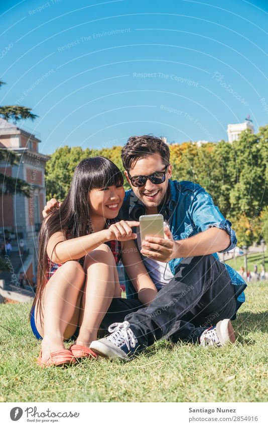 Young happy couple using smartphones in the park Beautiful Easygoing Solar cell Cellphone Chinese Communication Connection Copy Space