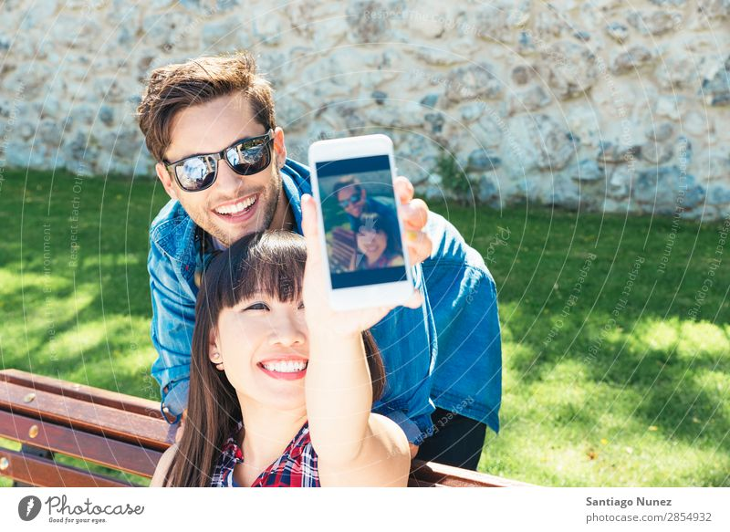 Young happy couple using smart phone in the park asian Beautiful boyfriend Easygoing Solar cell Cellphone Chinese Communication Connection Copy Space Couple