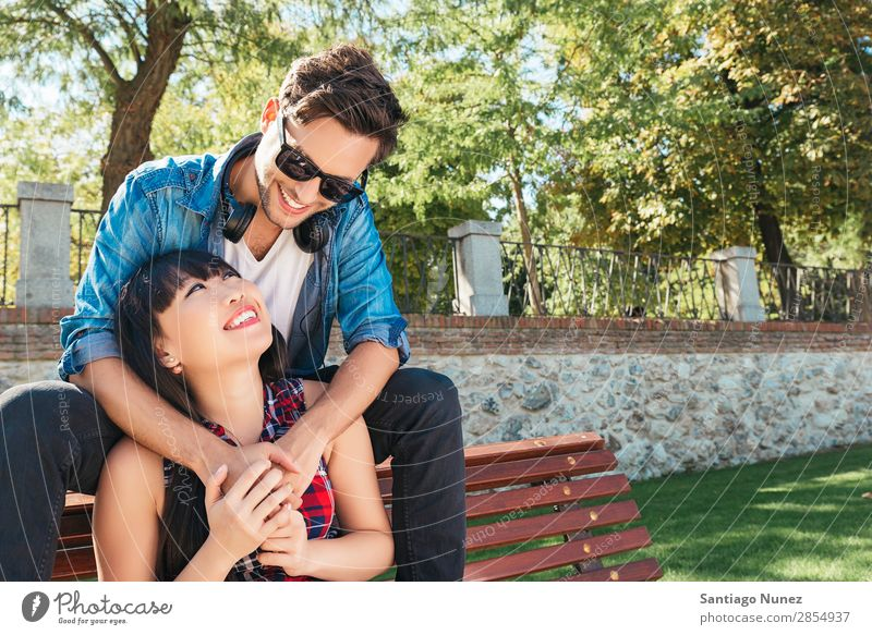 Young happy couple using smart phone sitting in the park asian Beautiful boyfriend Easygoing Solar cell Cellphone Chinese Communication Connection Copy Space