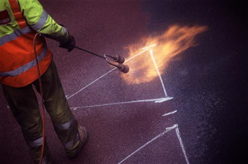 Road Painting Flame Torch Work and employment Craftsperson Craft (trade) Man Adults Street Workwear Protective clothing Pants Jacket Boots Yellow Orange paint