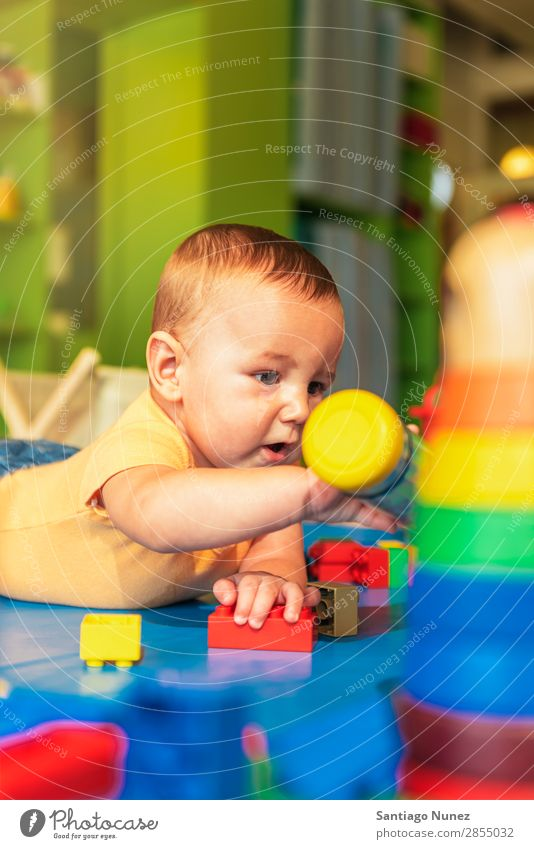 Happy baby playing with toy blocks in the kindergarten. Baby Playing childcare Kindergarten School Toys Toddler Boy (child) Small Child Considerate Story Cute