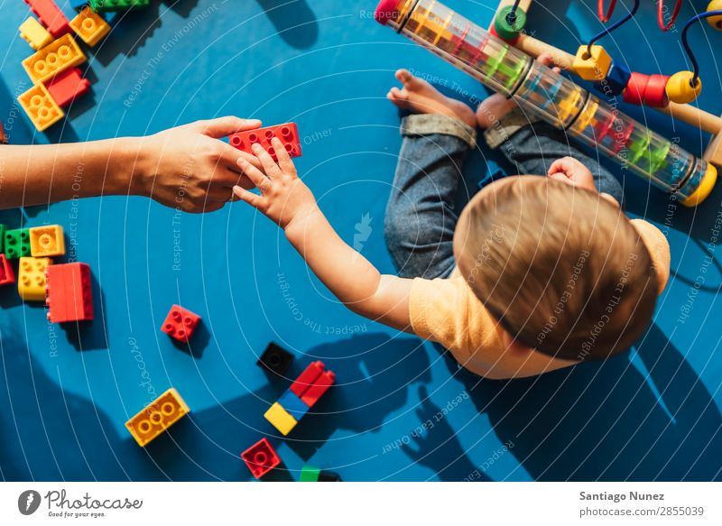 Happy baby playing with toy blocks. Baby Playing childcare Kindergarten School Toys Mother Teacher Help mum Toddler Boy (child) Small Child LEGO Considerate