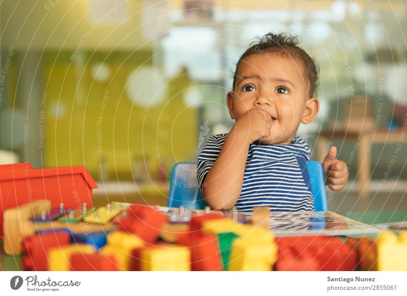 Happy baby playing with toy blocks. Baby Playing childcare Kindergarten School Toys Toddler Girl Small Child Smiling Considerate Cute Joy Preschool Education