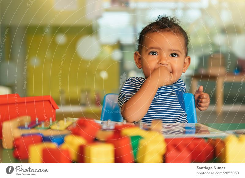 Happy baby playing with toy blocks. Baby Playing childcare mulatta multiethnic Kindergarten Portrait photograph School Toys Toddler Girl Small Child Considerate