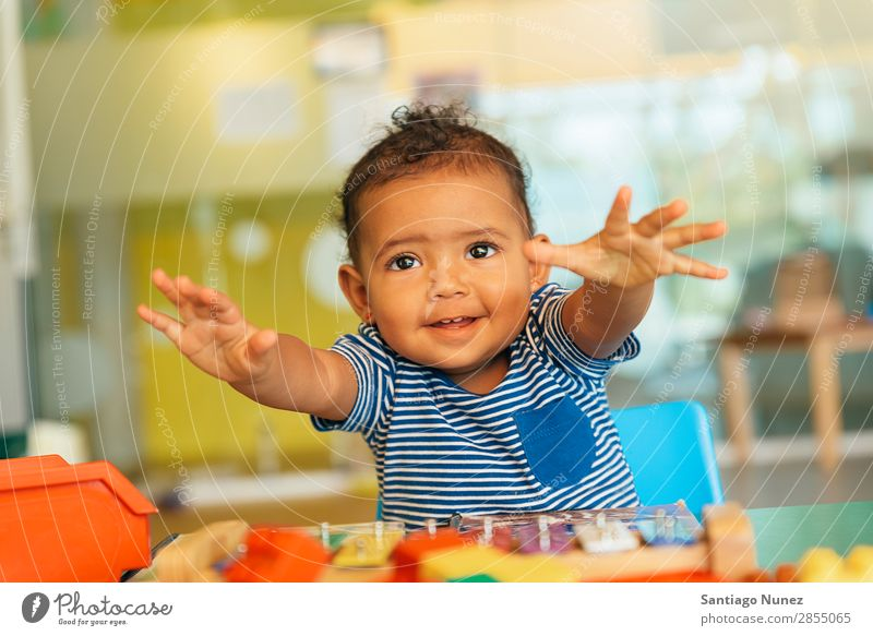 Happy baby playing with toy blocks. Baby Playing childcare Kindergarten School Toys Toddler Girl Small Child Smiling Considerate Cute Embrace Lifestyle Joy
