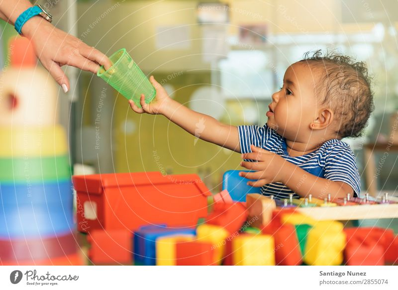 Happy baby drinking water and playing. Baby Playing childcare Kindergarten School Toys Toddler Girl Small Child blocks Considerate Story Cute Joy Preschool