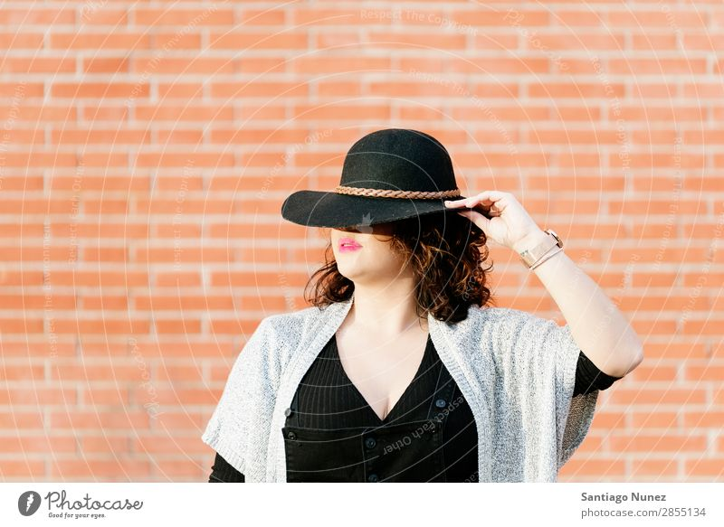Blonde hipster posing with straw hat against orange brick background. Fashion Wall (building) Girl big size Hip & trendy Woman Youth (Young adults) Hipster