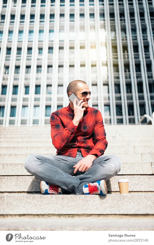 Young man with mobile phone in the city. Mobile Man Telephone Hipster Lifestyle Stand City Building Solar cell PDA Town Human being handsome Style Street Coffee