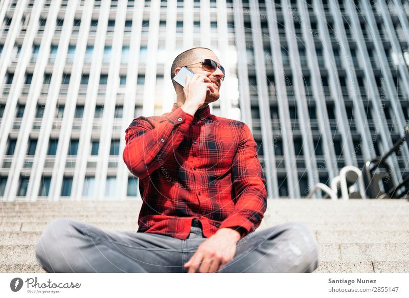 Young man with mobile phone in the city. Mobile Man Telephone Hipster Lifestyle Stand City Building Solar cell PDA Town Human being handsome Style Street