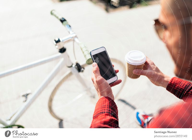 Young man using his mobile in the street. Mobile Man Portrait photograph Happy Smiling Telephone Hipster Lifestyle Stand City Solar cell Town Human being