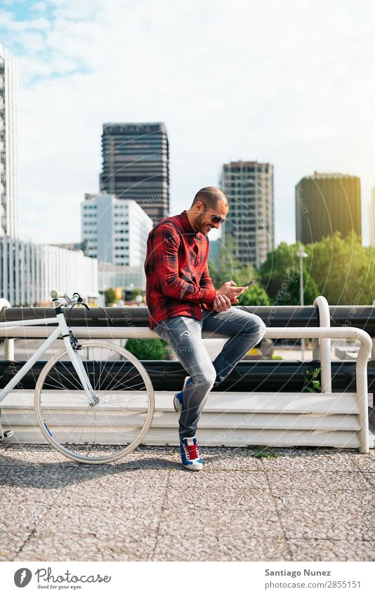 Young man with mobile phone and fixed gear bicycle. Mobile Man Bicycle fixie Telephone Hipster Lifestyle Stand Cycling City Building Solar cell Town Human being