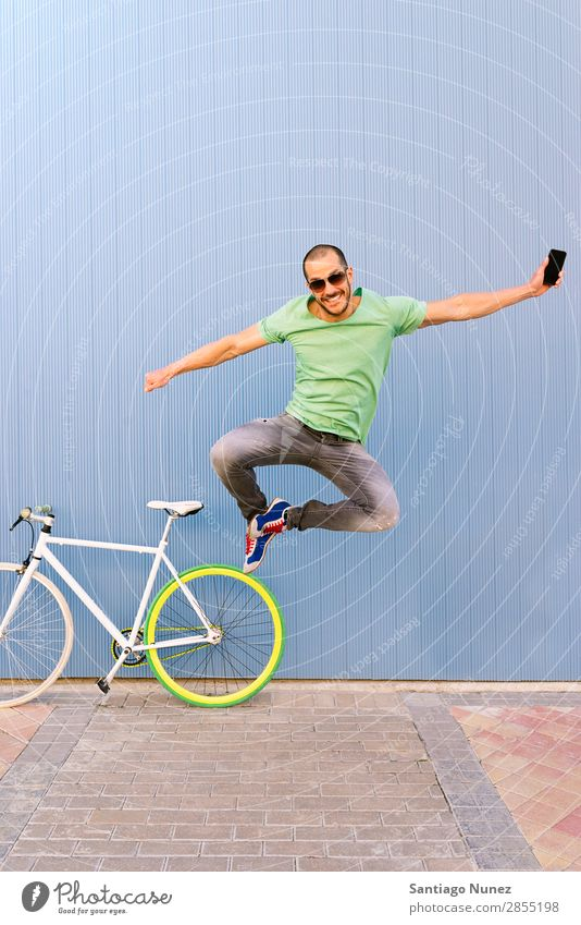 Outdoor portrait of handsome jumping. Man Jump Joy Smiling Bicycle fixie Telephone Hipster Lifestyle Stand Cycling City Town Human being Style Street PDA