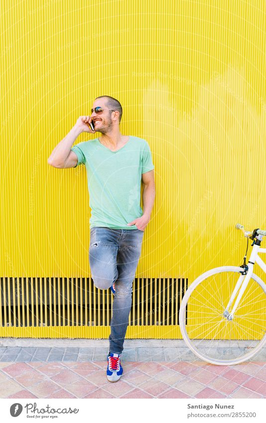 Handsome young man with mobile phone and fixed gear bicycle. Mobile Man Bicycle fixie Telephone Hipster Lifestyle Stand Cycling City Solar cell Town Human being