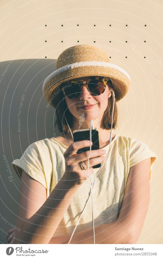 Beautiful young hipster Caucasian woman with smartphone and earphones, texting and listening to music. Easygoing Solar cell Cellphone Chat Headphones Woman Girl