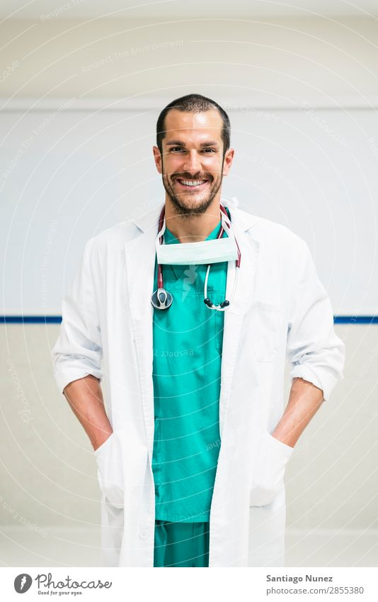 Smiling handsome doctor at hospital. Standing. Arm Background picture Considerate Caucasian Cheerful clinician Doctor Equipment Friendliness Happy Healthy