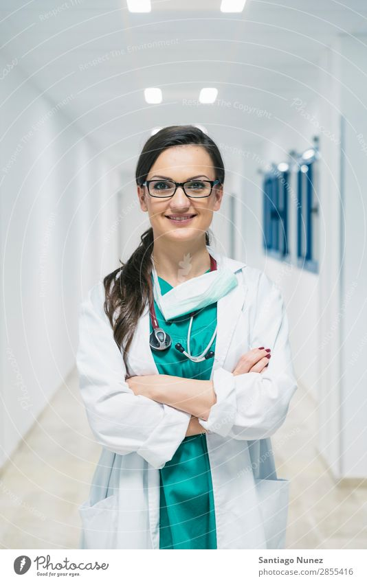 Smiling beautiful doctor at hospital. Standing. Arm Attractive Background picture Beautiful Considerate Caucasian Cheerful clinic clinician Doctor Equipment