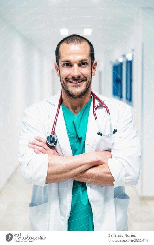 Smiling handsome doctor at hospital. Standing. Arm Background picture Beautiful Considerate Caucasian Cheerful clinic clinician Doctor Equipment Friendliness