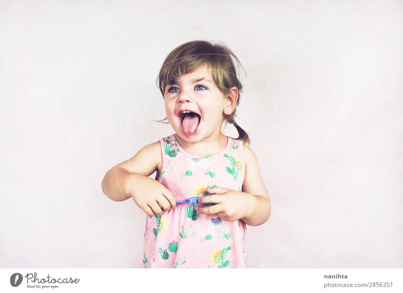 Young little and funny girl in a studio shot Lifestyle Joy Happy Face Child Human being Feminine Toddler Girl Infancy 1 1 - 3 years Dress Blonde To enjoy Brash