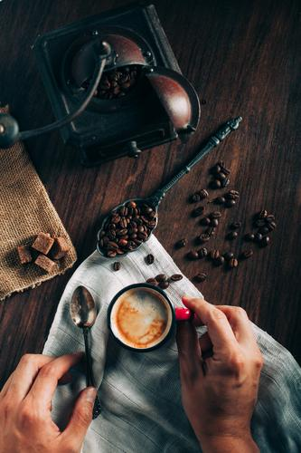 Closeup of hands takes a cup of espresso Coffee Espresso Black Fresh Strong Beans coffee beans coffee mill Antique Old Sugar Dice Brown Napkin Aromatic arabic