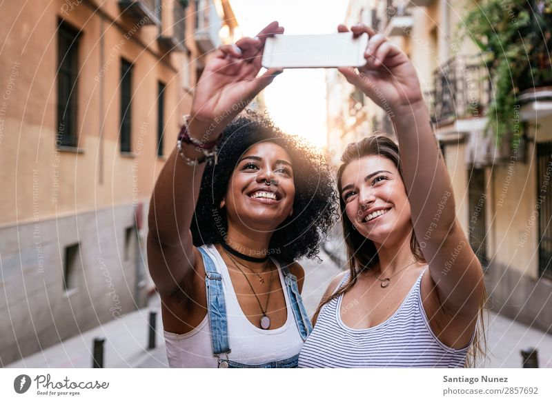 Beautiful women taking a self portrait in the Street. Woman Friendship Youth (Young adults) Happy Summer Human being Joy Mobile PDA Telephone Solar cell