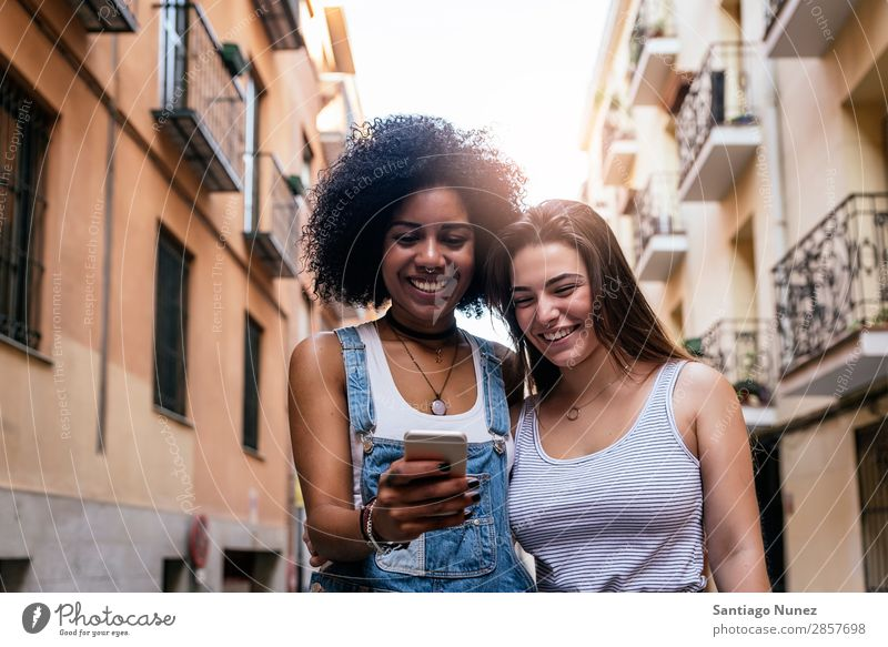 Beautiful women using a mobile in the Street. Woman Friendship Youth (Young adults) City Happy Summer Human being Joy Mobile PDA Telephone Solar cell