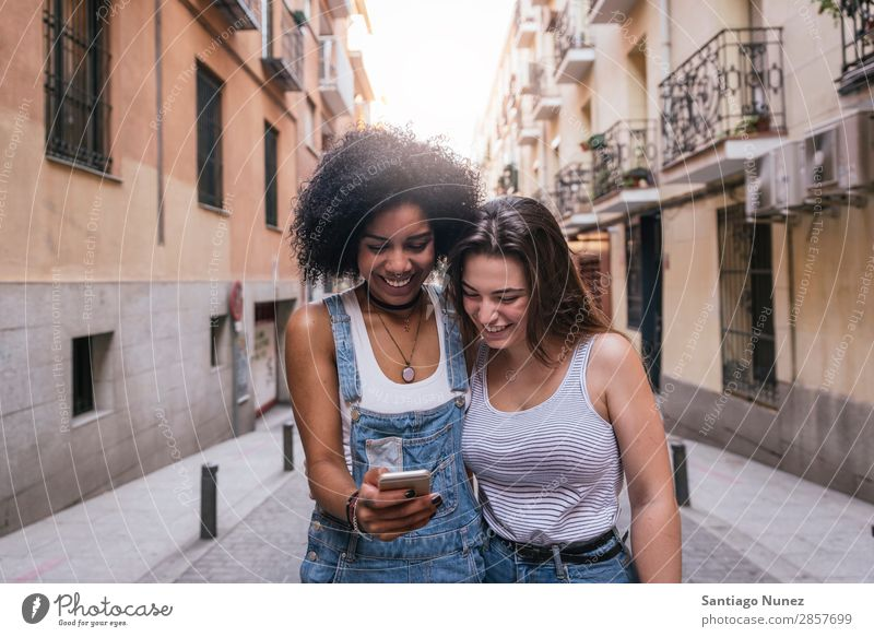 Beautiful women using a mobile in the Street. Woman Friendship Afro Youth (Young adults) Happy Summer Human being Joy